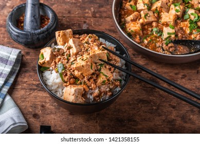 Popular Chinese Sichuan dish - a bowl of rice with spicy mapo tofu and a plate of mapo doufu on a rustic wooden table