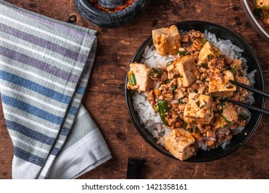 Popular Chinese Sichuan dish - a bowl of rice with mapo doufu on a rustic wooden table, top view