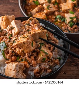 Popular Chinese Sichuan dish - a bowl of rice with mapo doufu on a rustic wooden table, top view, close-up