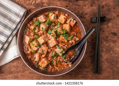 Popular Chinese Sichuan dish - a bowl of Mapo doufu on a rustic wooden table, top view