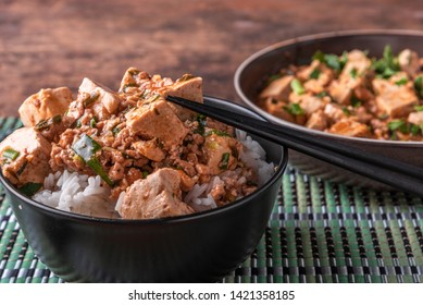 A popular Chinese Sichuan dish is a bowl of rice with spicy mapo tofu and a plate of mapo doufu on a bamboo napkin