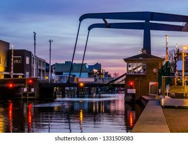 the popular city bridge alphensebrug in Alphen aan den Rijn, the Netherlands, beautiful water scenery at sunset