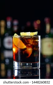 popular cocktail with rum cola - classic cube libre. Rum cola casual cocktail with ice cubes and lemon at festive bar stand background.