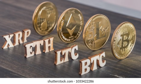 Popular cryptocurrency bitcoin, litecoin, ripplecoin and ethereum with text on wooden background.