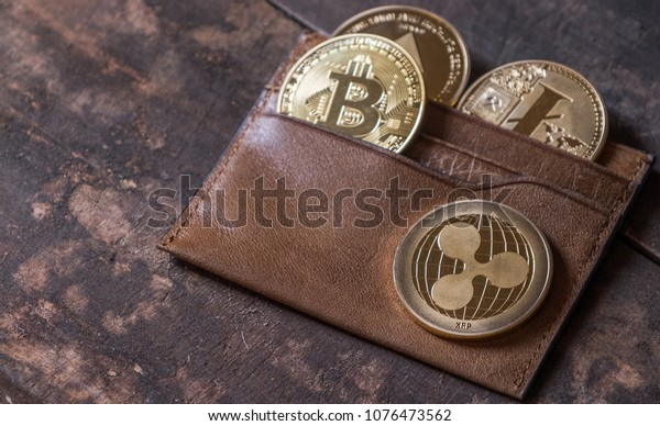 Popular cryptocurrency in leather wallet on wooden table top