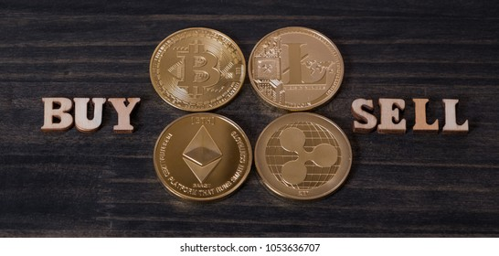 Popular cryptocurrency litecoin, bitcoin, ripple coin and ethereum with BUY and SELL words on wooden background