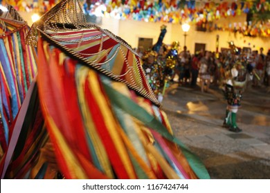 Popular culture. Bumba-meu-boi do Maranhão: dance typical of the June festivals. In the foreground, an individual dances with a colorful hat. In the background, colored flags blurred. Brazil.