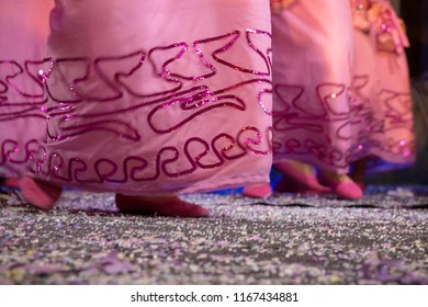 Popular culture. Carnival of Recife. Pernambuco, Brazil. Feet of two women dancing on the floor with confetti. Frevo block apparel. Pink dress with embroidery of sequins.
