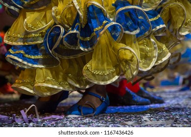 Popular culture. Carnival of Recife. Pernambuco, Brazil.Feet of a woman dancing on the floor with confetti. Frevo block clothing in blue, yellow and gold colors. Shoes blue.