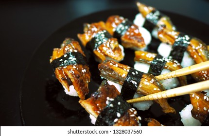 Popular delicious japanese food, Sushi set placed on a black plate, Fresh eel pieces with rice and nori topped with sweet sauce and decorated with white sesame seeds. Eat with chopsticks.