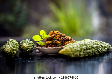 Popular dish for serving in lunch i.e. Bitter gourd with spices and vegetables on wooden surface in a glass plate with raw karela,Close up view.