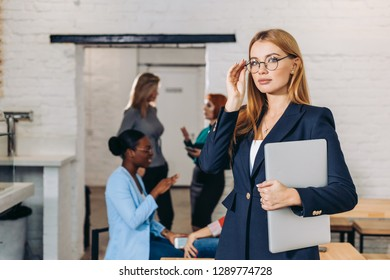 Popular female bloger in spectacles and formal wear holding laptop, thinking about new post, while looking at camera, posing in office with her colleagues on background