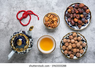 Popular food during Iftar  - macadamia nuts, pistachios, walnuts, dry dates. Karan, rosary, teapot, bowl with black tea on concrete background Top view Flat lay Muslim holiday of holy month of Ramadan