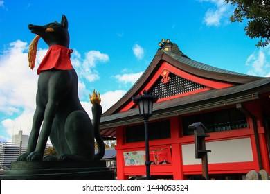 Popular fox (kitsune in Japanese) statue in front of the red Fushimi Inari Taisha shrine. Kyoto, Japan, Asia.