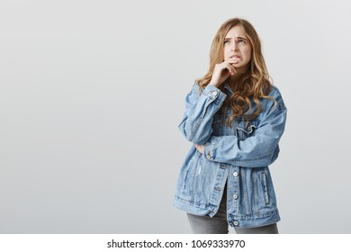 Popular girl not good at math. Confused bothered cute blonde woman in stylish denim jacket biting finger while frowning and looking up, trying to recall important thing or being anxious of issue