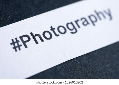 """Popular hashtag """"photography"""" printed on white paper on blue background."""