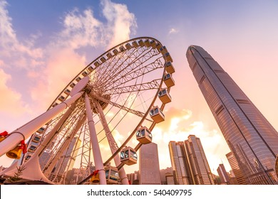 The popular icon Observation Wheel in Hong Kong island at sunset near Ferry Pier arera with landmark buildings in background.