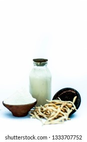 Popular Indian & Asian ayurvedic herb isolated on white in a clay bowl i.e. Musli or safed musli or Chlorophytum borivilianum with its powder in a clay bowl and raw milk in a transparent glass bottle.