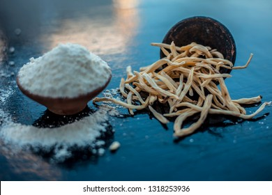 Popular Indian & Asian ayurvedic organic herb musli Safed Moosli/ Shaqaqule/ Dholi Musli/ Khiruva/ Shedheveli/ Swetha Musli/ Taniravi Thang/ in a clay bowl on wooden surface with its powder also.