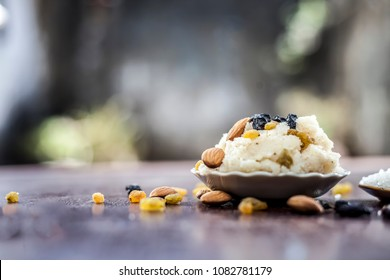 Popular Indian and Asian dessert Suji ka halwa or Rava with organic almonds, cashews and black & golden raisns in a clay bowl on wooden surface.