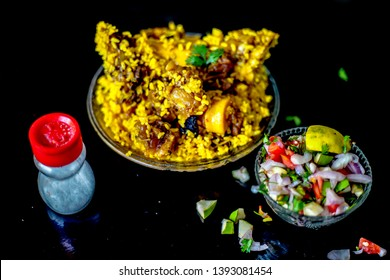 Popular Indian & Asian kashmiri dish i.e. yakhni or akhni in a glass plate along with some salad and salt on black colored shiny surface.