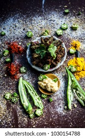 Popular Indian Brunch dish i.e Barali bindi/crispy okra or bharli bindi  a dish made from raw ladies finger and other vegetables with spices by frying it.On a wooden surface in dark Gothic colors.