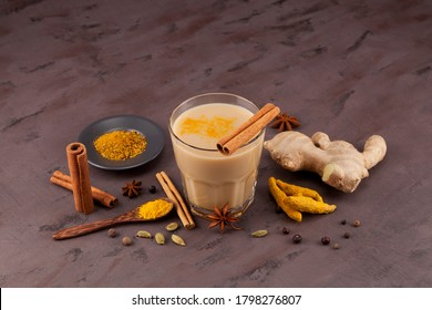 Popular Indian drink  Karak tea or Masala chai. Prepared with the addition of milk, variety of spices and spices. Transparent cup on a brown textured background next to the ingredients.