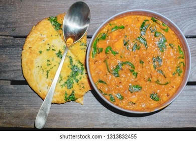 Popular Indian food vegetarian and vegan lentil dahl tadka curry soup with ginger, fresh coriander, sweet potato and coconut milk served with roti flatbread close-up on a vintage wooden table