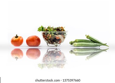 Popular Indian Lunch dish isolated on white i.e. Bhareli Bhindi or bareli bindi or fried crispy stuffed okra,with raw okra pods and tomatoes.