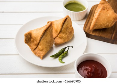 popular indian snack called veg Samosa, favourite tea time snack served with tamarind and mint chutney or tomato ketchup and green fried chilli