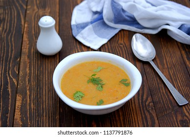 Popular Israeli orange soup cream with pumpkin, carrots, sweet potato and red lentils on a wooden background