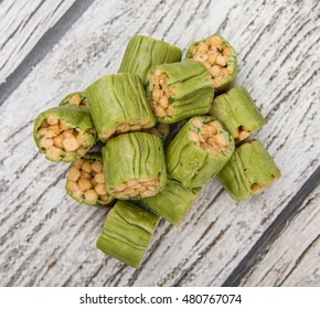 Popular Japanese snack small pieces of sweet, deep fried flour with brown sugar (karinto), wrapped with thick matcha skin over wooden background