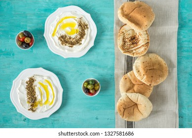 Popular middle eastern appetizer labneh or labaneh, soft goat milk cheese with olive oil, olives, zaatar or hyssop and pita bread served over rustic turquoise wooden table, top view