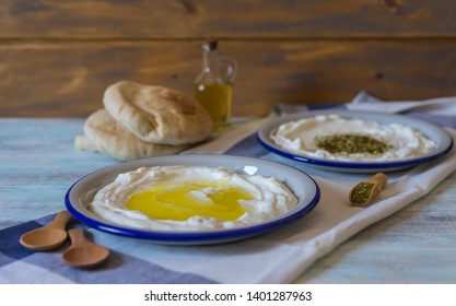 Popular middle eastern appetizer labneh or labaneh, soft goat milk cheese with olive oil, zaatar or hyssop and pita bread served over rustic turquoise wooden table, sideway view