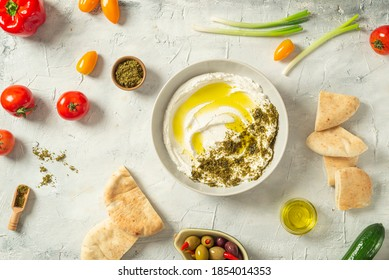 Popular middle eastern appetizer labneh or labaneh, soft white goat milk cheese with olive oil, hyssop or zaatar, served with many fresh vegetables on a wooden plate over grey table, flaylay.
