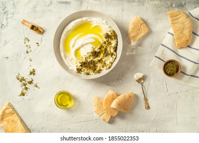 Popular middle eastern appetizer labneh or labaneh, soft white goat milk cheese with olive oil, hyssop or zaatar, served with pita bread over grey table, flaylay.