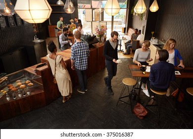 Popular modern coffee shop busy with customers and staff