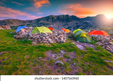 Popular mountain wild camping area, spectacular camp with colorful tents. Stunning sunset in mountains with campground, Retezat mountains, Transylvania, Romania, Europe