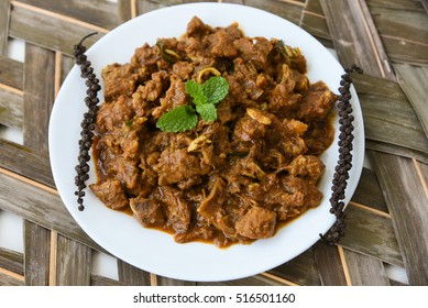Popular mutton/lamb/beef steak/meat roast/fry hot and spicy curry dish on a coconut leaf mat. Kerala, India. Food prepared using Indian spices.