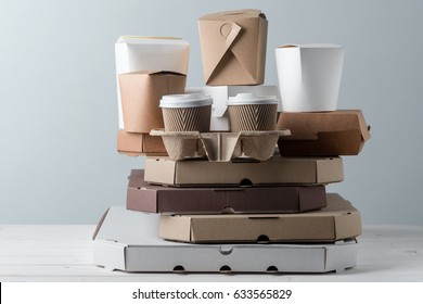 Popular paper food containers, take-out coffee cups in holder and pizza boxes, close-up. Grey background, wooden surface. Food delivery.