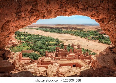Popular point of view of the valley of the desolating river Onila through a hole in a wall of Ancient Kasbah in Ait-Ben-Haddou, Morocoo. Famous ancient berber kasbah. near Ouarzazate city in Morocco