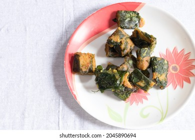 Popular recipe in the plate called as alu wadi made from long and big green leaves