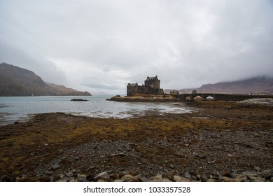 The popular scottish Eilean Donan castle  in the scenic landscape. The long Bridge leads to the entrance of the castle.
