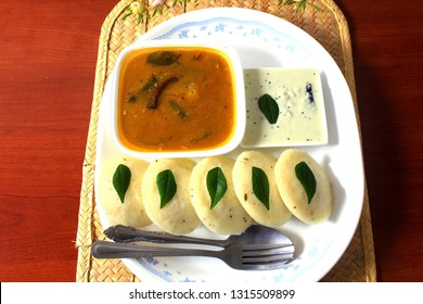 Popular South indian breakfast food Idli sambar or Idly sambhar made from rice and lentils steamed cakes with spicy soup Sambhar and green coconut chutney