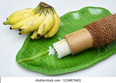 Popular South Indian breakfast Puttu or Pittu made of steamed rice flour and grated coconut  in the bamboo mould with banana Kerala, India. Sri lankan food