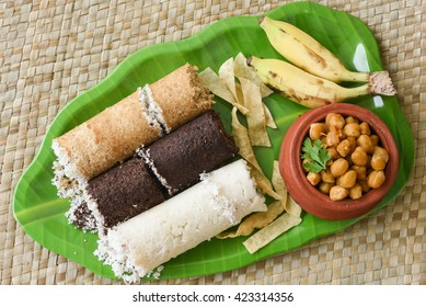 Popular South Indian breakfast puttu / pittu made of wheat, ragi / finger millet, white rice flour and coconut, with side dish chickpea / chana masala curry,banana and pappad / pappadom, Kerala, India