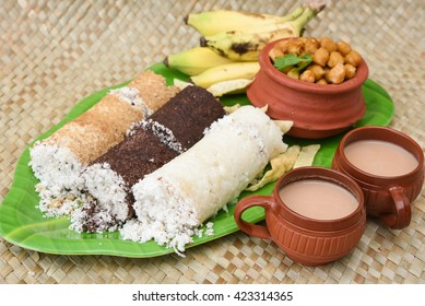 Popular South Indian breakfast puttu / pittu made of wheat, ragi / finger millet, white rice flour and coconut, with chickpea / chana masala curry, banana, pappad / pappadom and tea, Kerala, India.