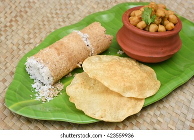 Popular South Indian breakfast puttu / pittu made of wheat flour and coconut, with chickpea / chana masala curry and pappad / pappadom, Kerala, India.