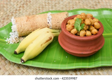 Popular South Indian breakfast puttu / pittu made of wheat flour and coconut, with chickpea / chana masala curry and banana, Kerala, India.