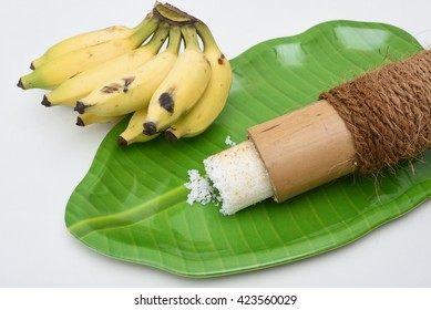 Popular South Indian breakfast puttu / pittu made of white rice flour and coconut, Kerala, India. Bamboo puttu prepared in the bamboo mould / utensil with banana.